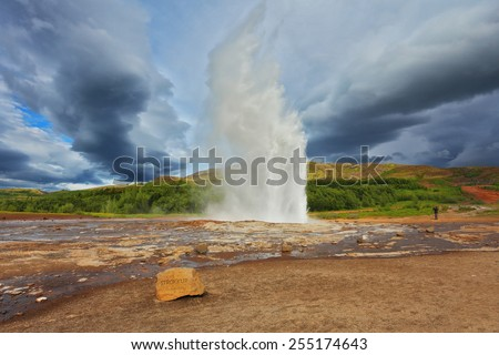 Gushing geyser Strokkur. High column of hot water and steam from the crater of the geyser. Iceland in the summer - stock photo