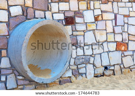 gutter in a stone wall on the beach side construction - stock photo