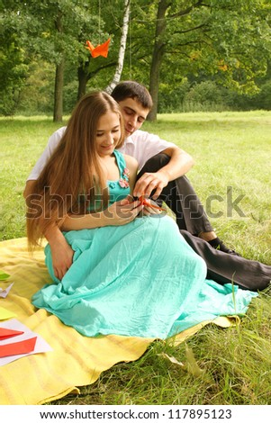 guy and girl doing origami at a picnic in the park - stock photo