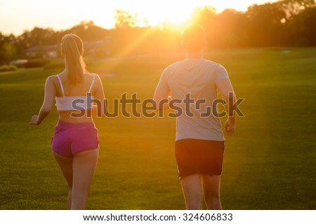 Guy and  girl running in the park. Morning running. Sports in nature. Morning cross-country on golf field. Boy and girl running cross-country. - stock photo