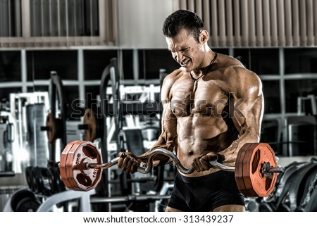 guy bodybuilder , execute exercise with weight in gym, horizontal photo - stock photo