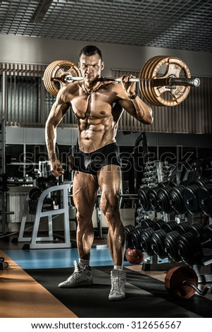 guy bodybuilder , execute exercise with weight in gym, vertical photo - stock photo