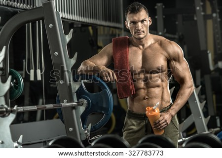 guy bodybuilder tired in gym hold shaker with sportive nutrition - protein of shaker , vertical photo - stock photo