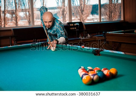 guy concentrating on breaking pyramid of balls in the table angle. American pool billiard. Pool billiard game. Billiard sport concept. - stock photo