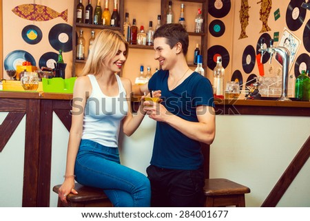 guy flirting with a blonde in a bar and gives her a cocktail. horizontal photo - stock photo