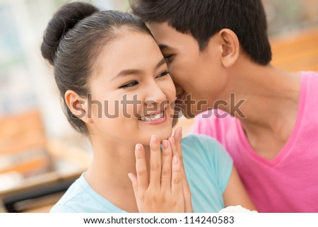 Guy flirting with his girlfriend whispering in her ear with tenderness - stock photo