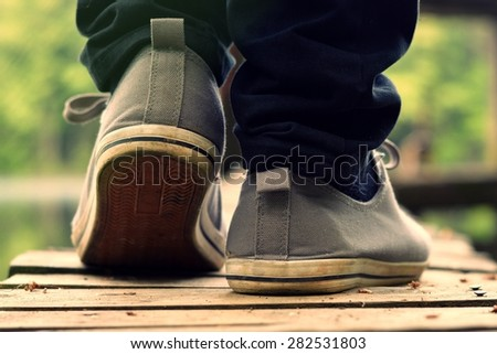 Guy goes in sneakers on the pier - stock photo