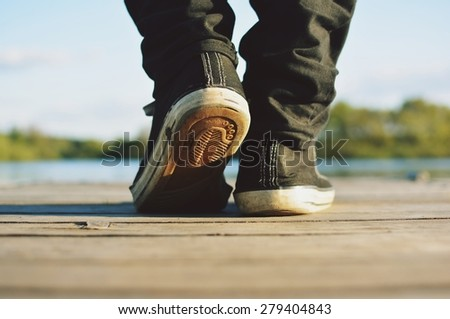 Guy goes in sneakers the pier - stock photo