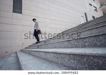 Guy going down the stairs from the work - stock photo