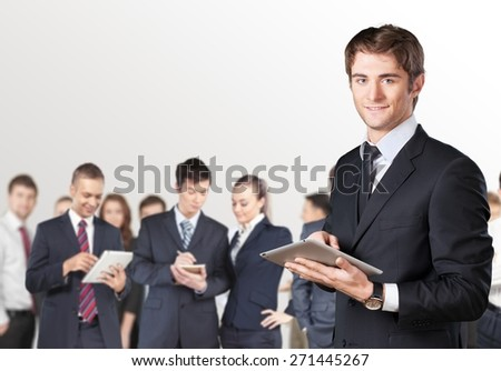 Guy. Happy smiling young businessman using his digital tablet at the office - stock photo