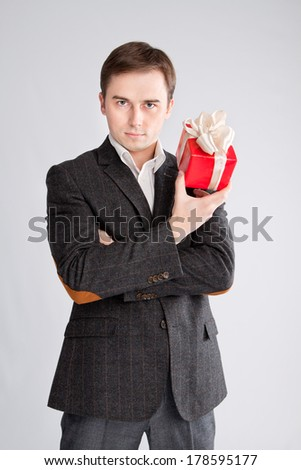 guy holding a gift near the face, a stern look - stock photo