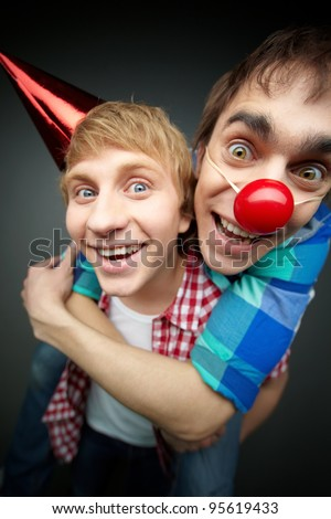 Guy holding his friend piggyback at a fool�s day party - stock photo
