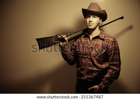 guy in a hat with a gun. cowboy style. portrait. - stock photo