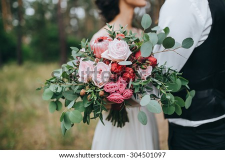 guy in a white shirt and waistcoat and a girl in a white wedding dress with a bouquet of red flowers and greens in hands stand in a clearing in the woods - stock photo