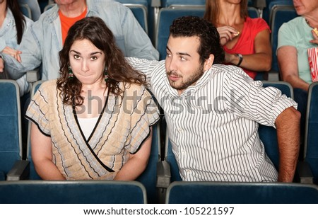 Guy in beard flirts with young woman in theater - stock photo