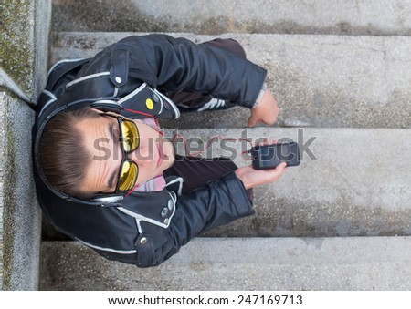 Guy in leather jacket listening to music with mobile phone and headset. - stock photo