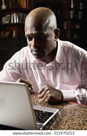 Guy in tense expectancy state while sittin at the table and looking to laptop screen - stock photo