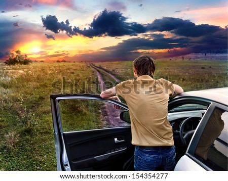 guy is standing near car and looking at the sunset - stock photo
