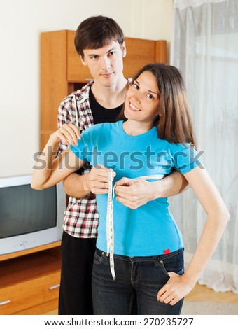 Guy measuring bust of girlfriend with measuring tape at home  - stock photo
