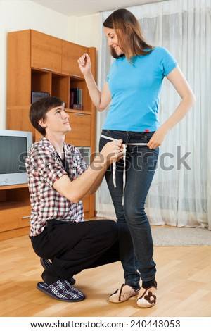 Guy measuring butt of girl with measuring tape - stock photo