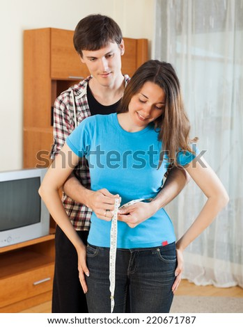 Guy measuring waist of girlfriend with measuring tape at home - stock photo