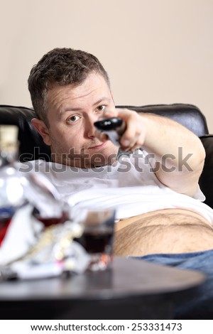Guy on the couch flips channels on tv - stock photo