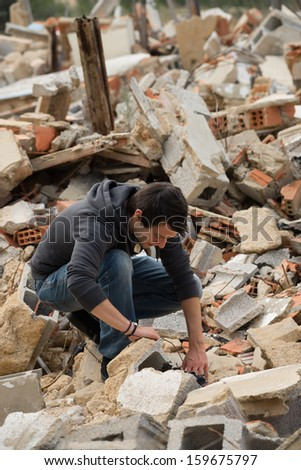 Guy rummaging in a whole lot of construction debris - stock photo