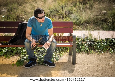 Guy sitting on a park bench  with a bottle of wine - stock photo