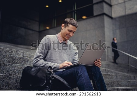 Guy sitting on steps and working with laptop. - stock photo