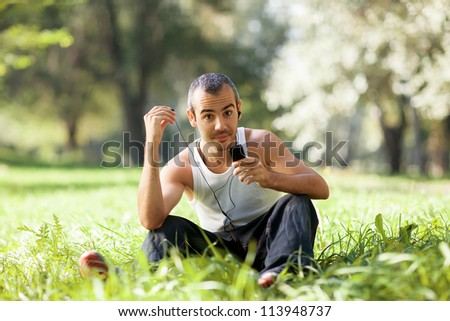 guy sitting on the grass listening to the player and stares - stock photo