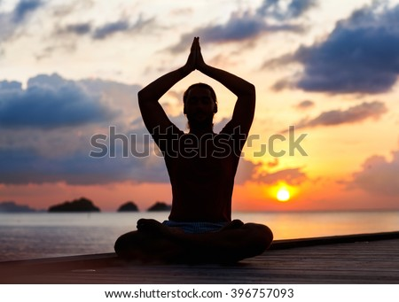 guy sitting on the sea and is engaged in yoga - stock photo