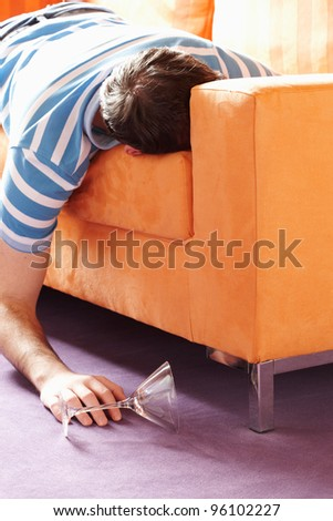 guy sleeping on the sofa with a glass on the floor - stock photo