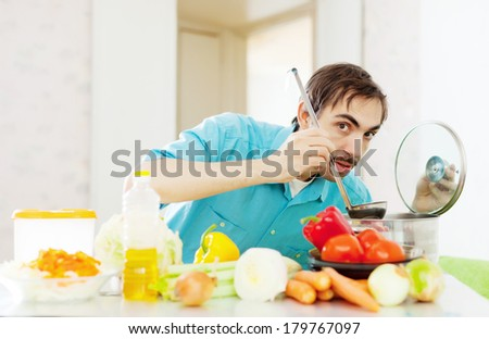 guy tasting   soup with ladle from pan in kitchen - stock photo