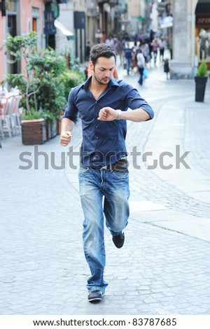 guy that runs late into town and watch the clock - stock photo