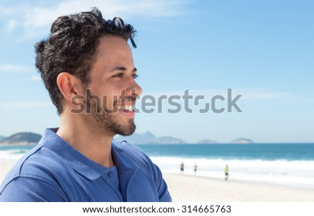 Guy with beard and blue shirt at beach looking sideways - stock photo