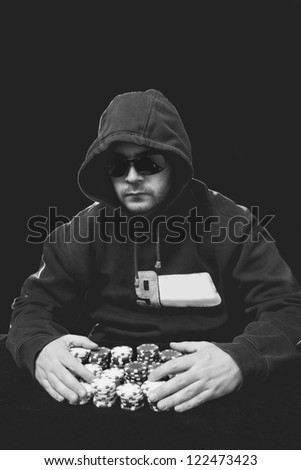 guy with glasses playing poker with chips in his hands - stock photo