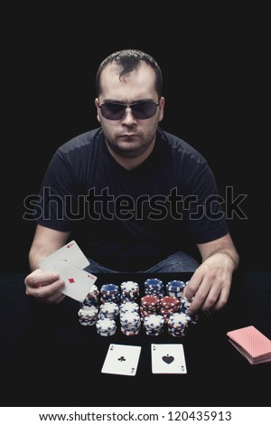 guy with glasses playing poker with two aces in his hands - stock photo