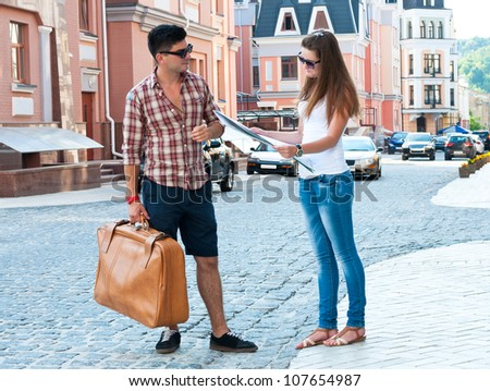 Guy with suitcase and girl with map on street. - stock photo