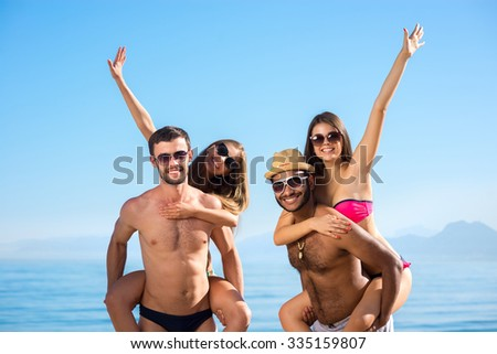 Guys and girls enjoyed holiday. In love couple on vacation. Weekend on the islands. Young people sunbathing on the beach. Young people smiling. Summer vacation at the resort. - stock photo