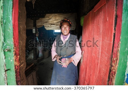 GYANTSE, TIBET - JUNE 2: Tibetan farmer in front of her house on 2 June, 2014 in Gyantse, Tibet. Farmers in Tibet have a low income of just 1800 US dollars per year.  - stock photo