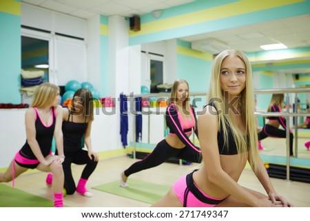 Gym. Alluring female athletes warming up - stock photo