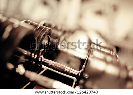 Gym equipment background with close up selective focus to a dumbbell weight stacked on a rack with plenty of blurred copyspace - stock photo