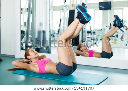 Gym fitness woman working out doing press fitness exercise smiling happy during workout. Young fitness model training in fitness center. - stock photo