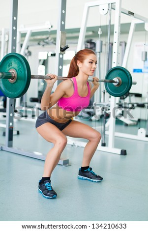 Gym fitness woman working out doing weight training smiling happy during workout. Young fitness model training in fitness center. - stock photo