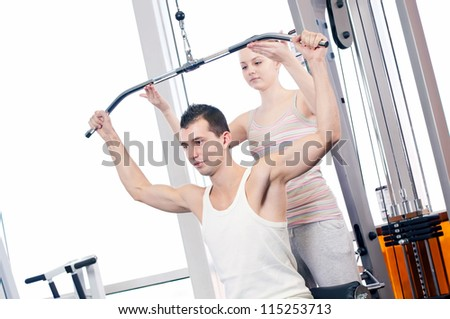 Gym man and woman doing exercise at the fitness club. Personal trainer. - stock photo