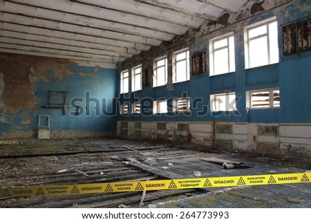 Gym of the abandoned School in Chernobyl Zone. Ukraine. Signs of radiation hazard - stock photo