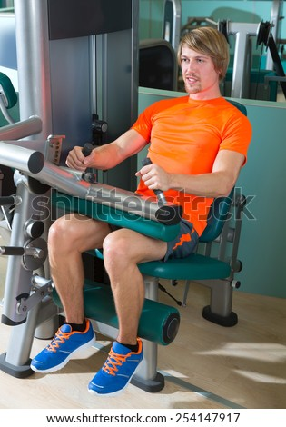 Gym seated leg curl machine exercise blond man at indoor - stock photo