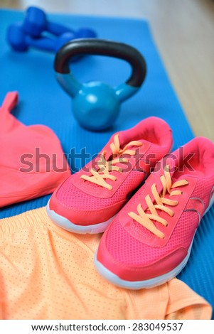 Gym shoes - Fitness outfit closeup with kettlebell. Crossfit workout clothes on yoga mat in pink neon color with weights in the background on the floor. Fashion activewear clothes concept. - stock photo