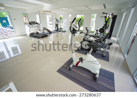 Gym with power dumbell lifting, stationary bicycle standing and elliptical cross trainers equipment - stock photo