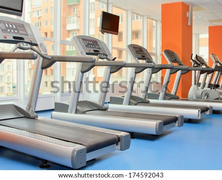 Gym with windows and running machines in fitness center - stock photo